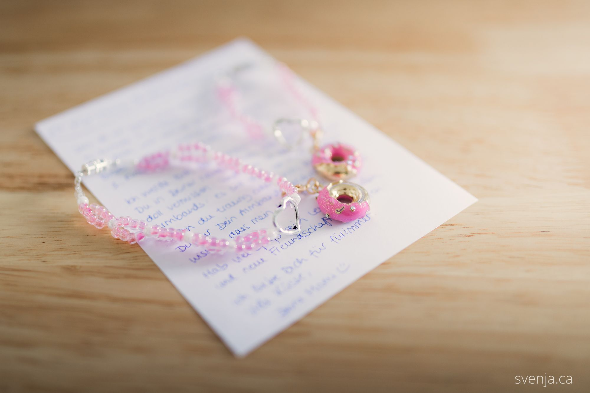 two pink bracelets lay on top of a handwritten note