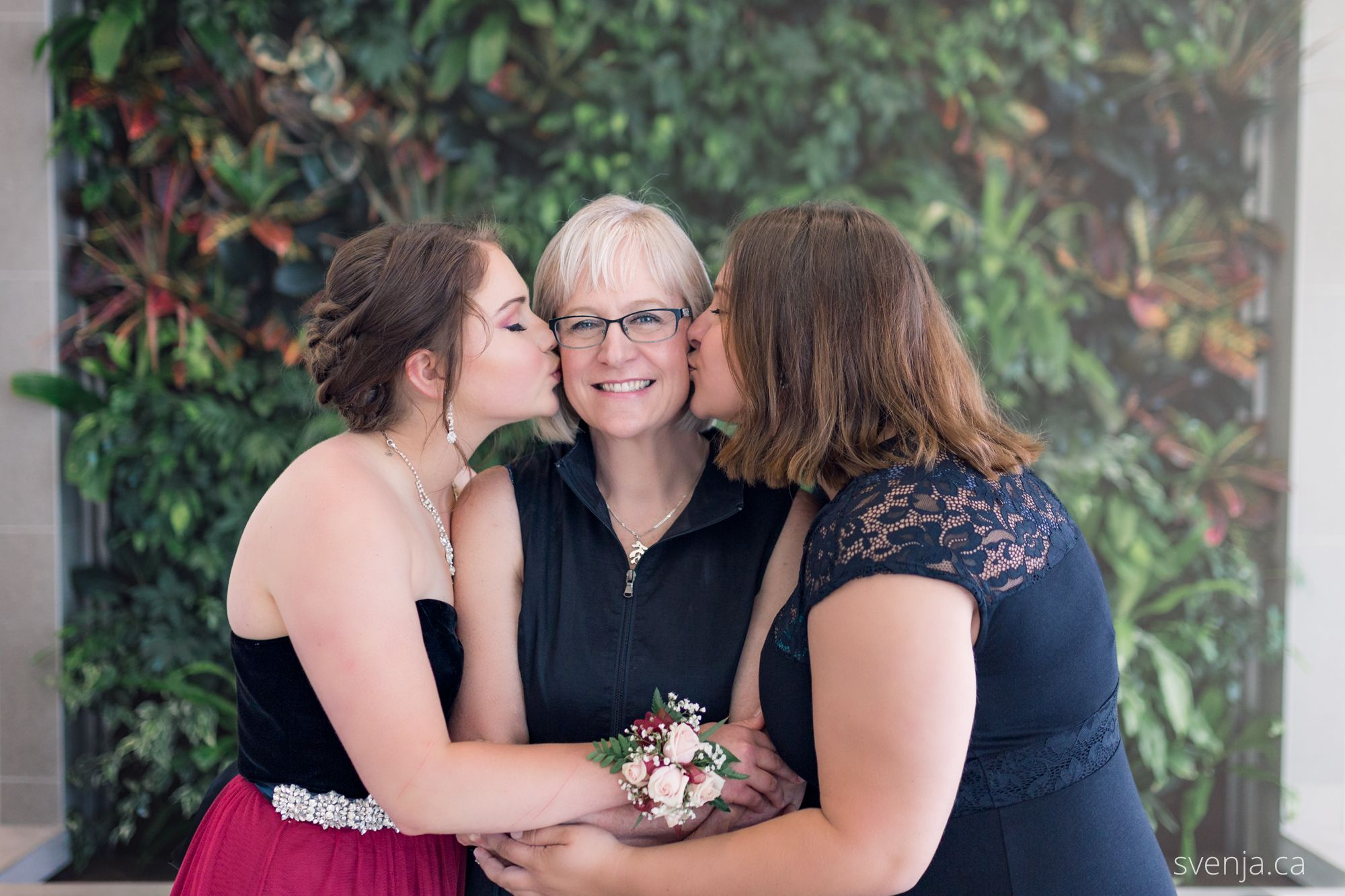 mom with two daughters in front of a green plant wall
