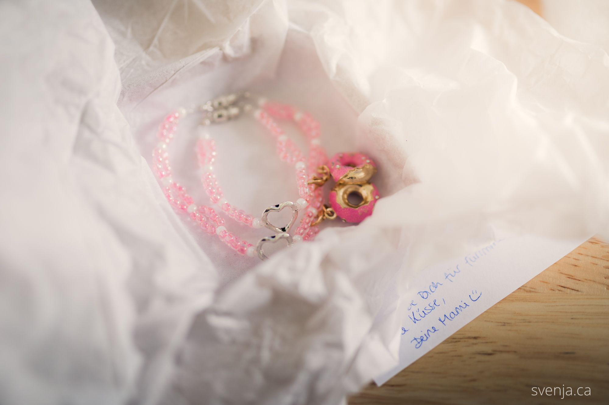 two pink bracelets lay in an opened box