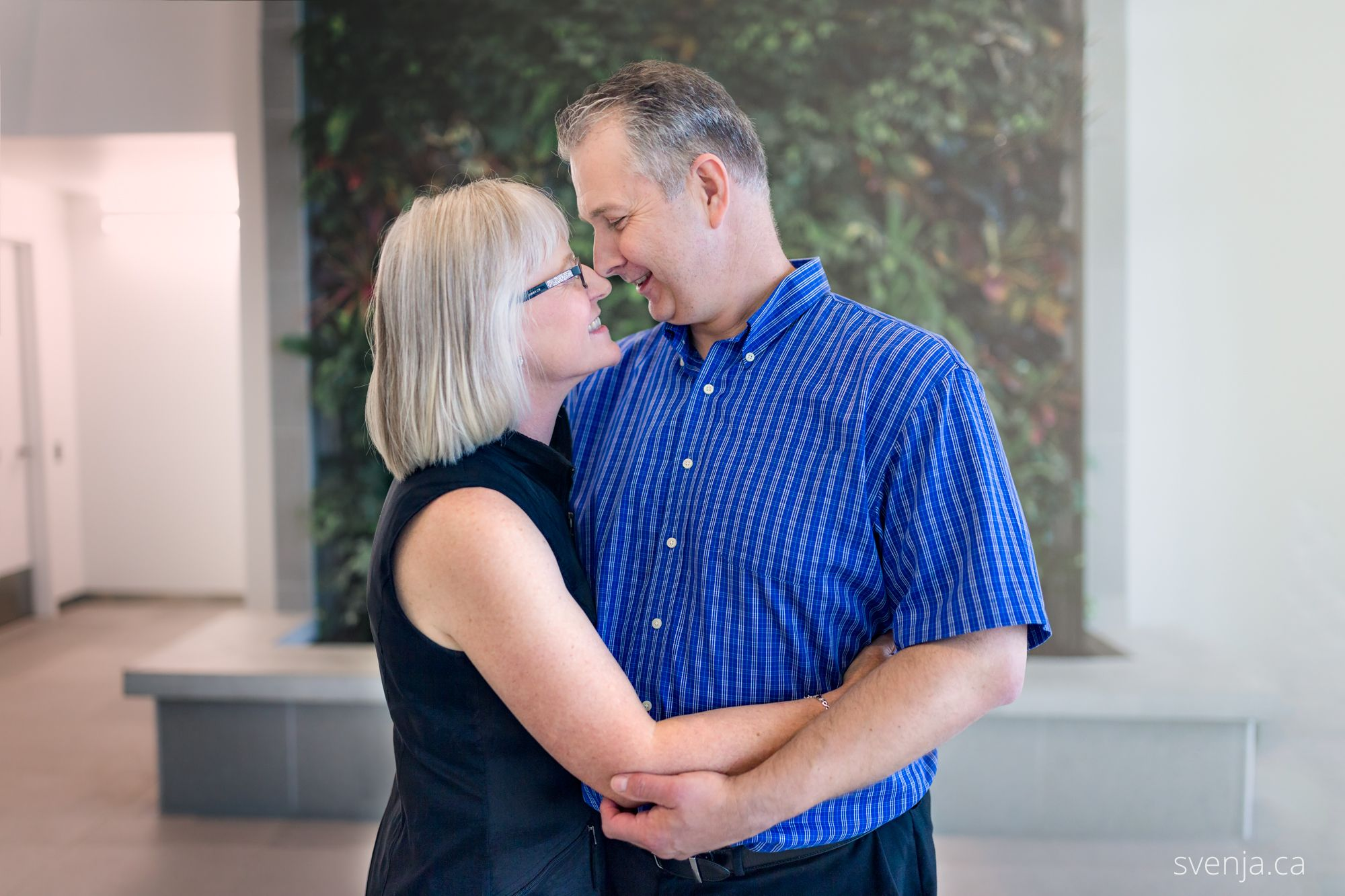 couple embracing in front of a green plant wall