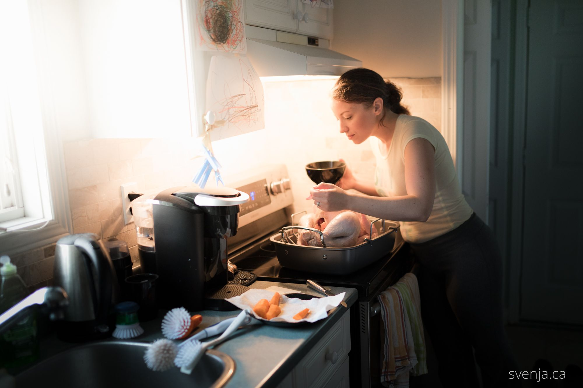 woman seasoning a turkey in a kitchen
