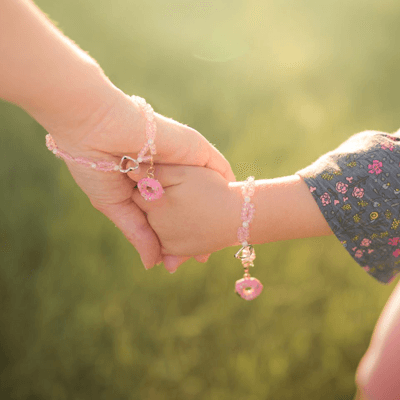 a parent and child hold hands while wearing a pink bracelet thumbnail