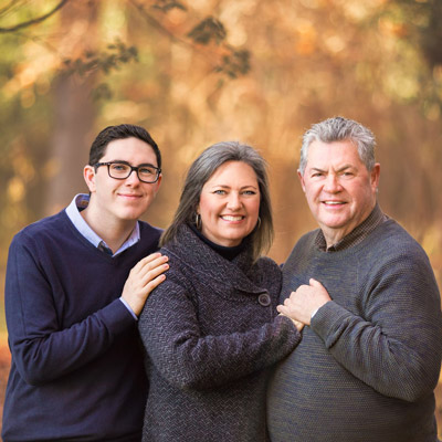 son, mother and father stand smiling in front of a forest